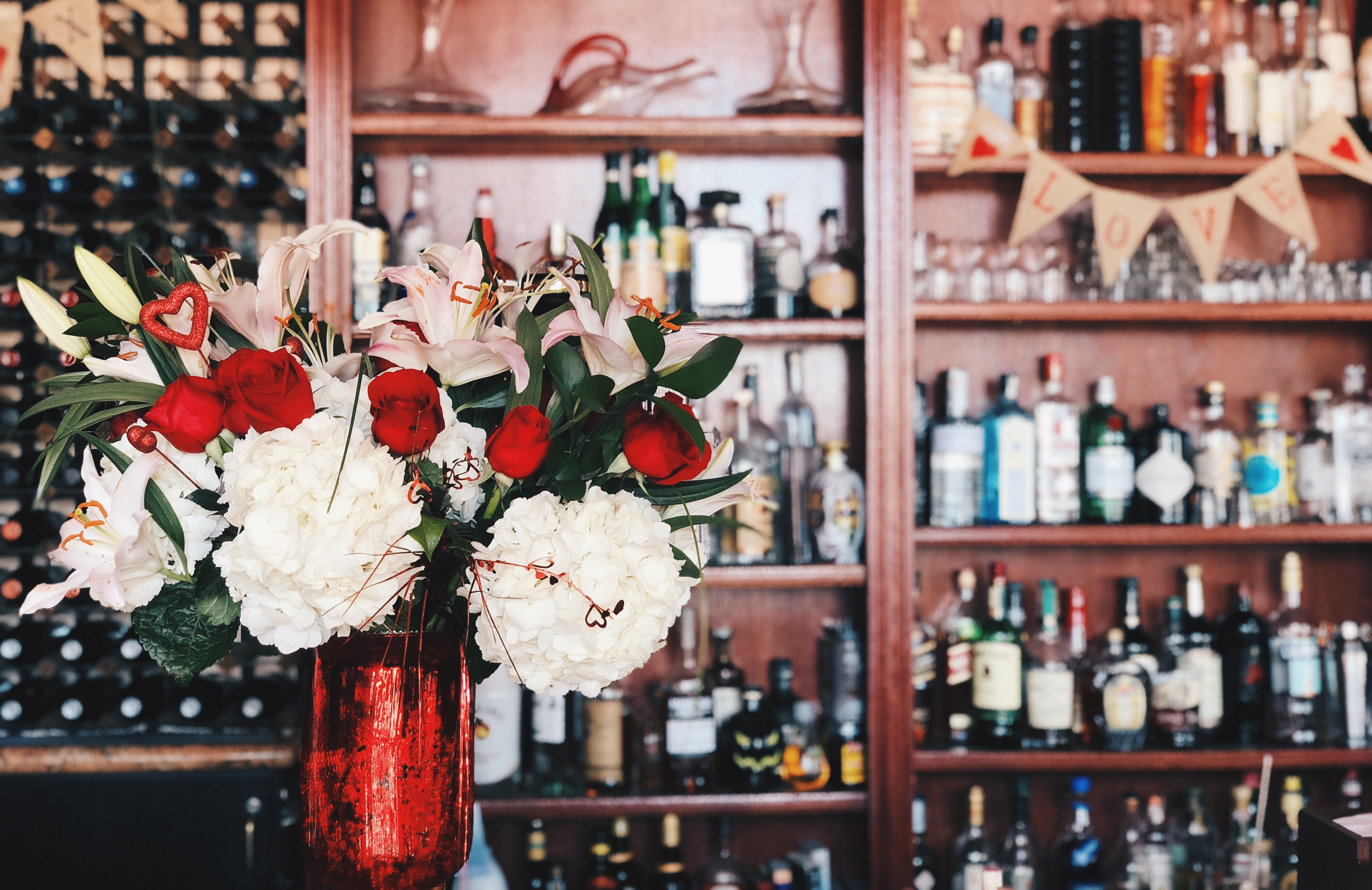 Red and white flower bouquet in a red vase in the foreground. The background is a blurred image of a full bar: Many bottles of vodka, gin, and  bourbon.