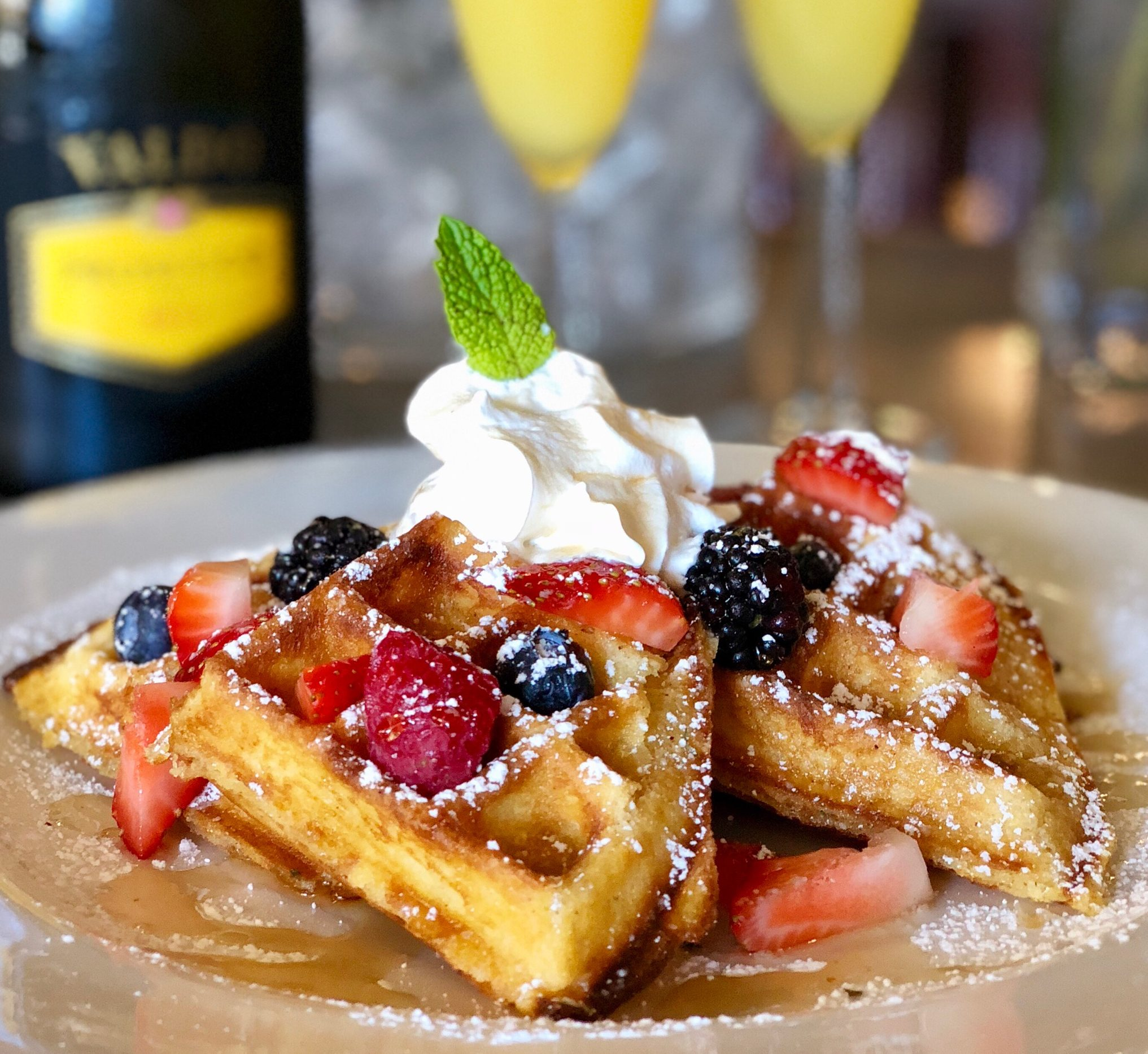 Brunch Belgium Wffles with fresh fruit, whipped cream, and mimosas