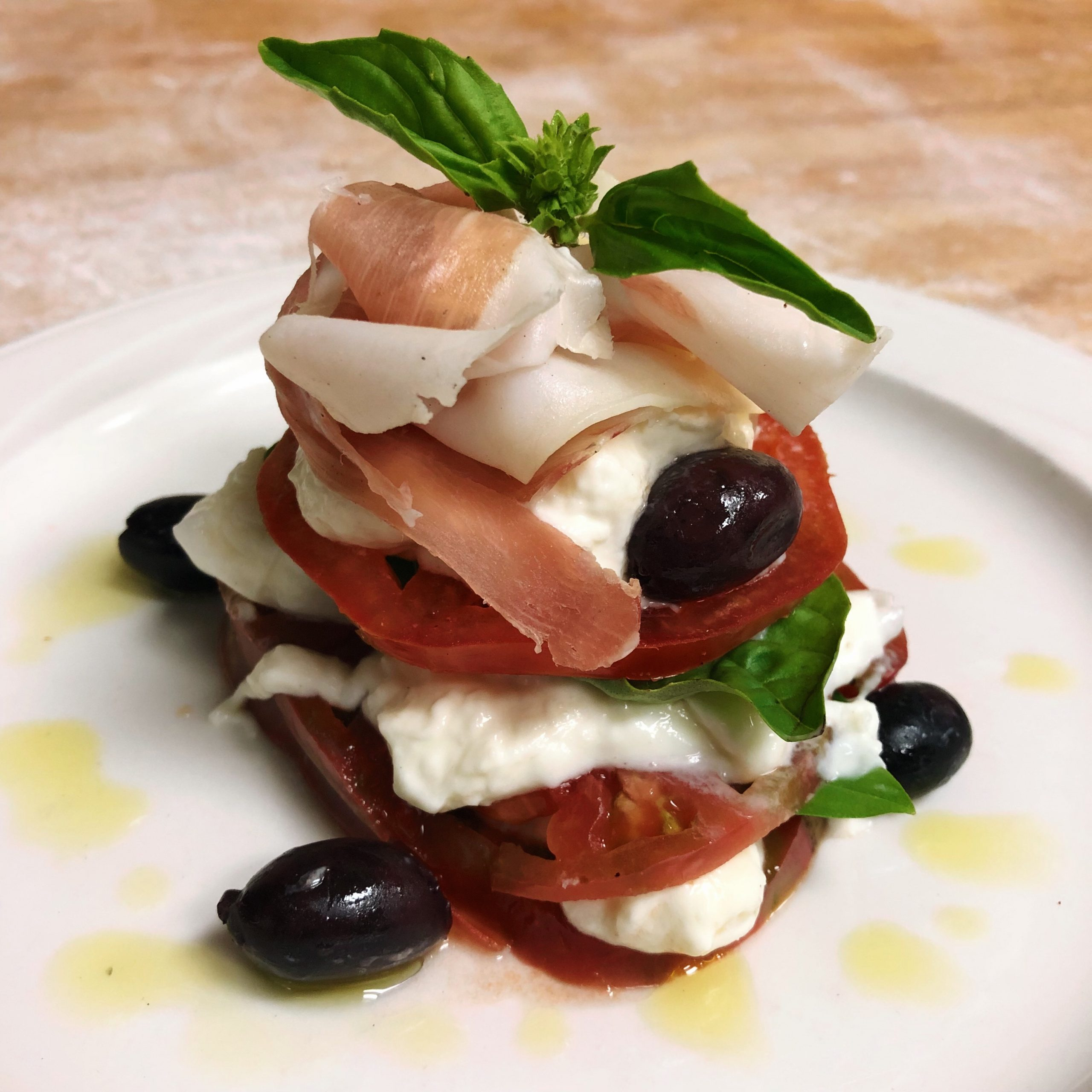 Burrata cheese layered with heirloom tomatoes, basil, prociutto, and served with mixed olives and olive oil