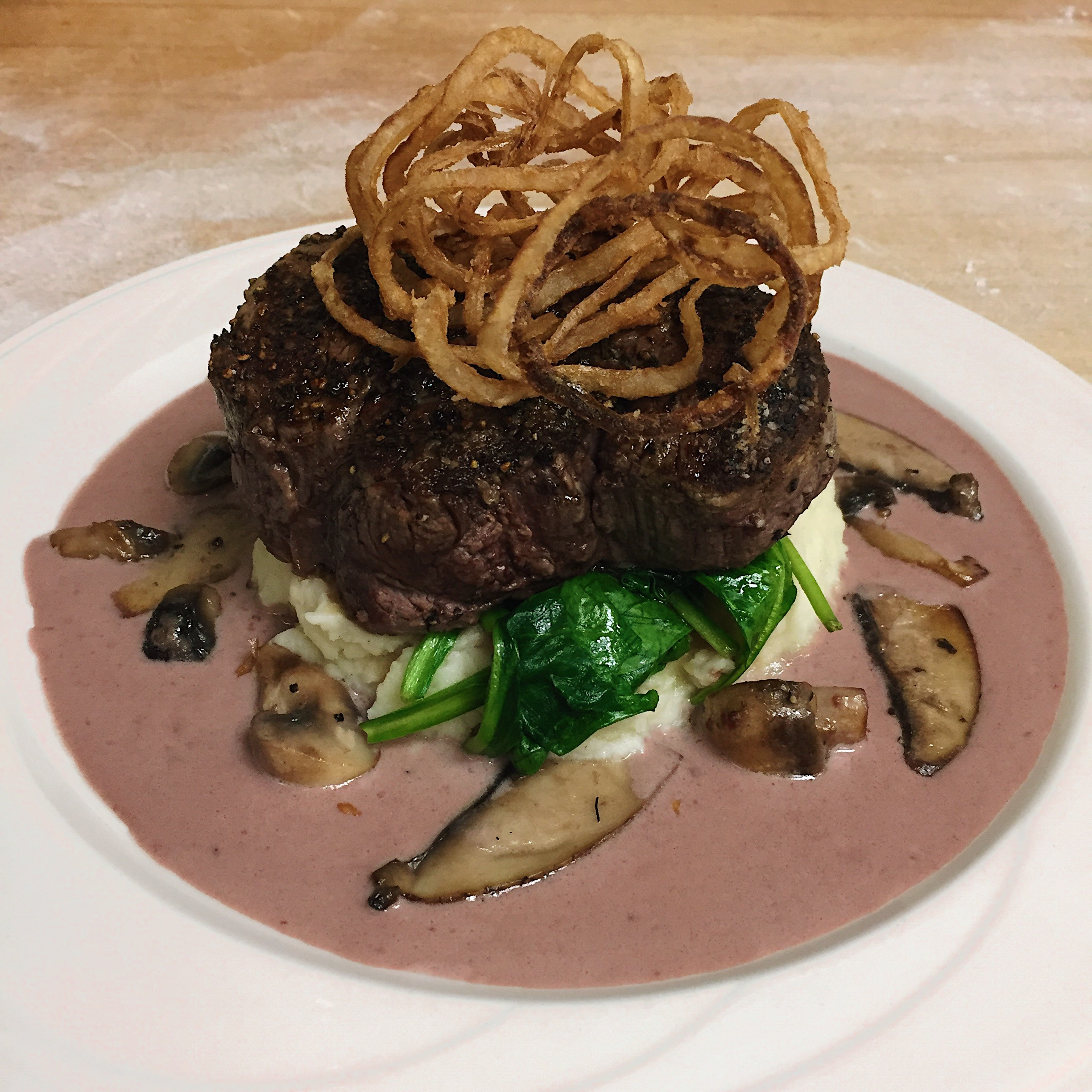 Filet Mignon served with mashed potatoes, sauteed spinach, and a cabernet reduction topped with fried onions