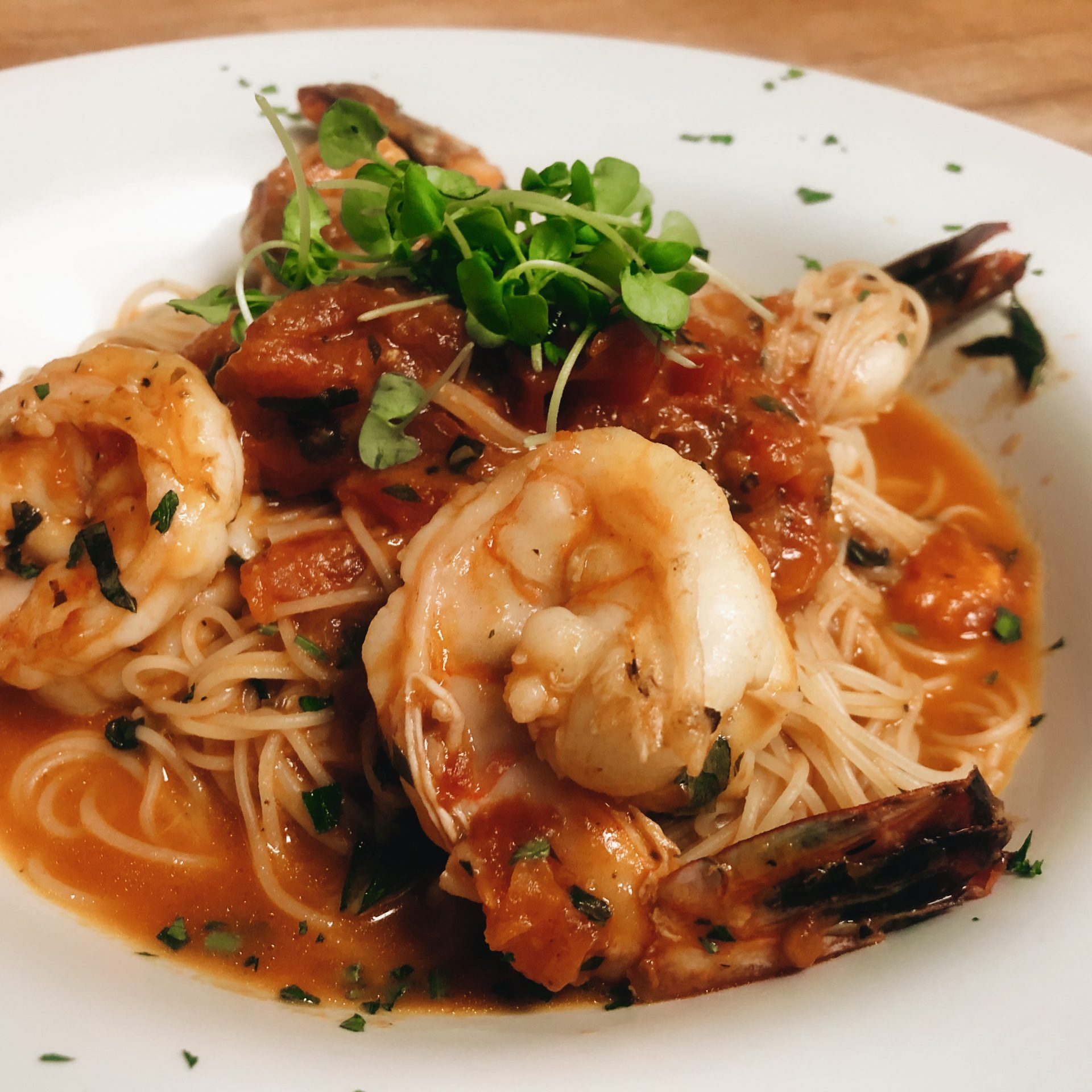 Jumbo Shrimp with angel hair pasta, roma tomatoes, and basil garnished with micro greens